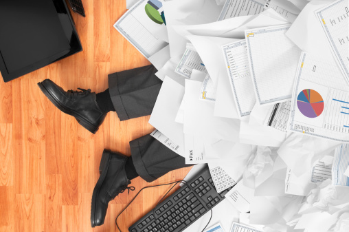 man buried in paper with keyboard falling on floor laying down