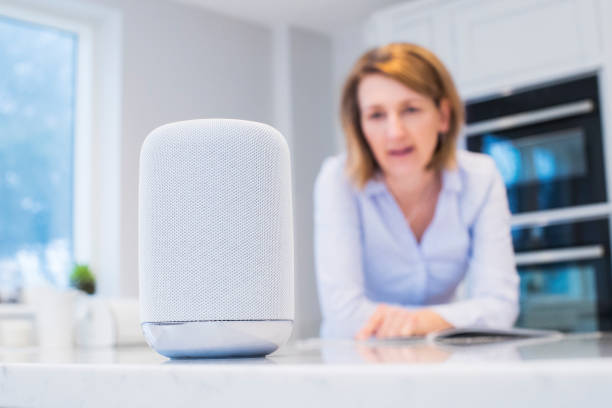 Woman In Kitchen talking Digital Assistant