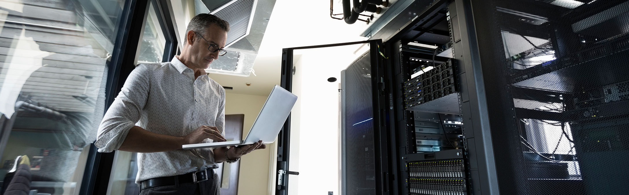 Man in server room holding laptop