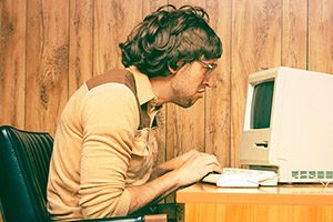 Funny image of man working on old mac computer