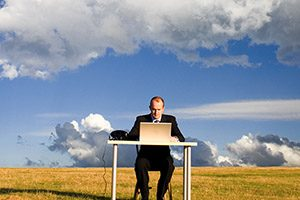 Man at desk in middle of field