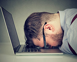 Man laying head on computer in frustration
